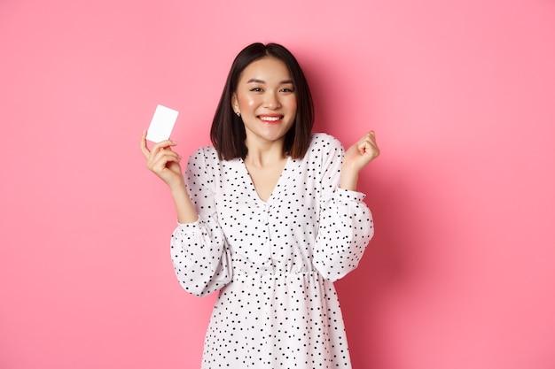Mulher asiática confiante e feliz segurando um cartão de crédito e sorrindo satisfeita