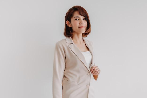 Mulher asiática confiante que trabalha com blazer bege isolado no branco