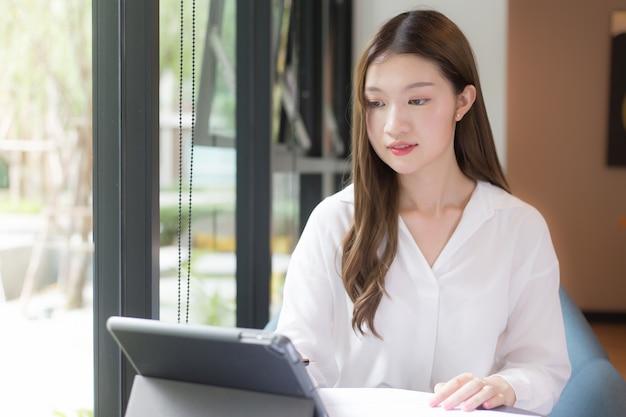 Mulher asiática confiante usar uma camisa branca está usando um tablet para trabalhar e há muitos documentos sobre a mesa. o rosto dela sorrindo em uma sala de trabalho em casa.