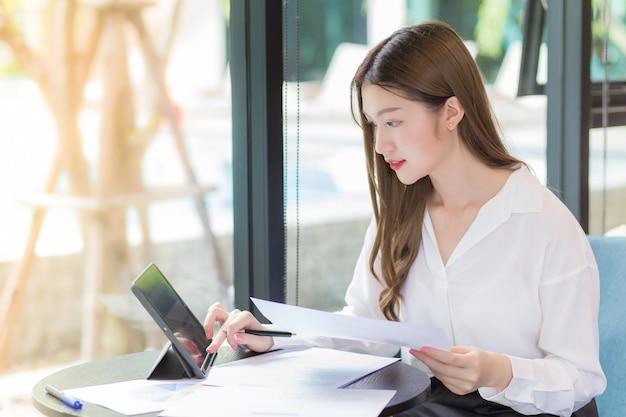 Mulher asiática confiante vestindo uma camisa branca está usando um tablet para trabalhar e há muitos documentos sobre a mesa. o rosto dela sorrindo em uma sala de trabalho em casa.