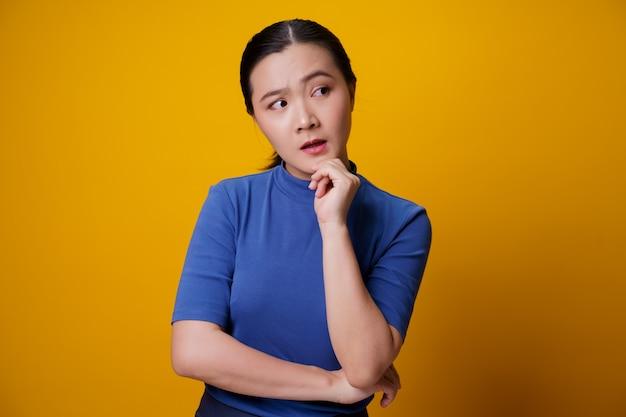 Mulher asiática confusa pensando e pisando em amarelo.