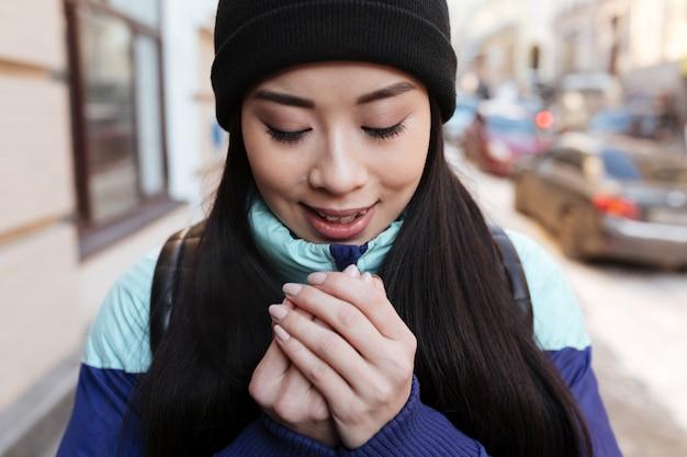 Mulher asiática congelada sorridente em roupas quentes