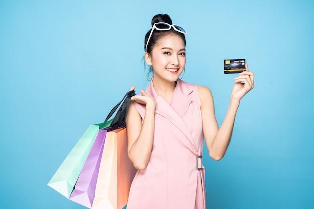 Mulher asiática consideravelmente bonito dos jovens que guarda o cartão de crédito e os sacos de compras com a cara do smiley que está no estúdio.