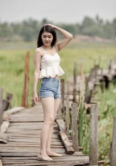 Mulher asiática consideravelmente nova que anda na ponte de madeira