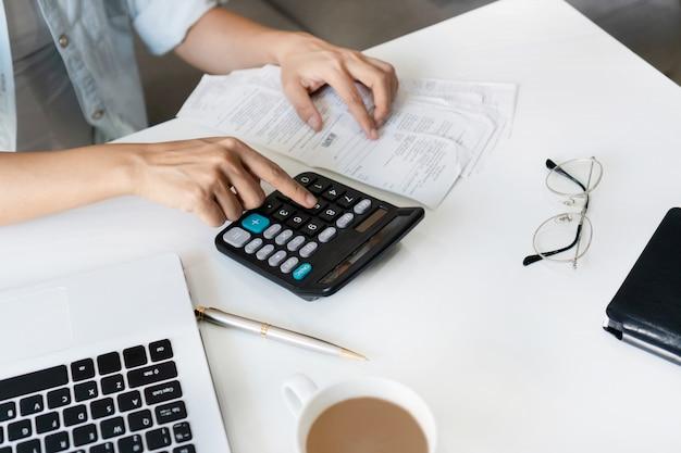 Mulher asiática consideravelmente nova que usa a calculadora para calcular despesas domésticas e imposto na sala de visitas em casa.