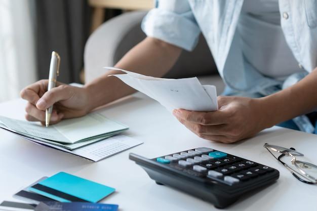 Mulher asiática consideravelmente nova que usa uma pena que escreve no livro de conta bancária ao guardar as contas para calcular despesas e impostos home na sala de visitas em casa.