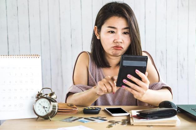 Mulher asiática, contando as despesas na calculadora
