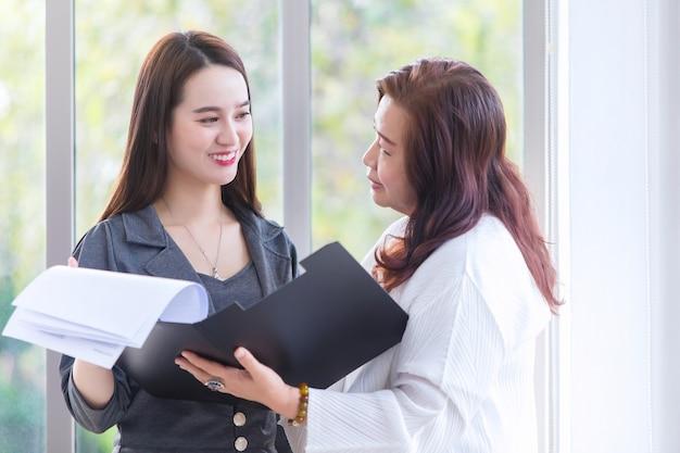 Mulher asiática conversa com sua chefe para consultar sobre o trabalho em um documento de arquivo em suas mãos