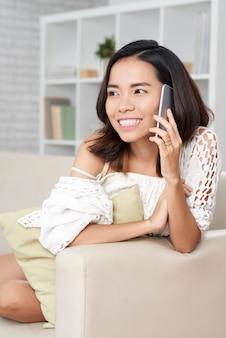 Mulher asiática, conversando no telefone, relaxando no sofá, olhando para longe