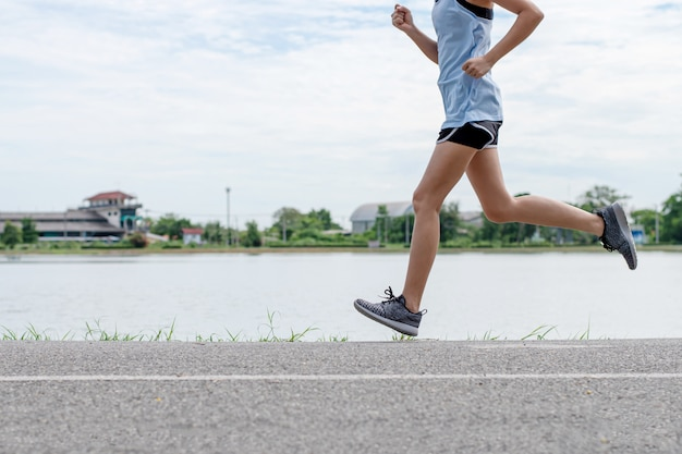 Mulher asiática correndo na estrada pela manhã.