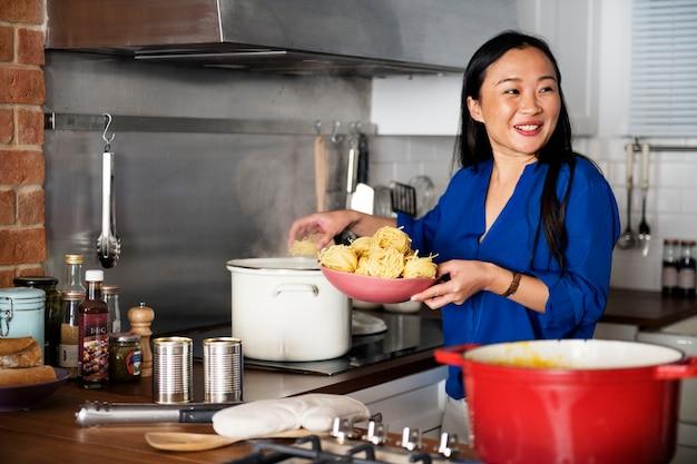 Mulher asiática cozinhar macarrão na cozinha
