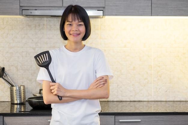 Mulher asiática cruzou os braços em pé na cozinha da casa segurando uma espátula