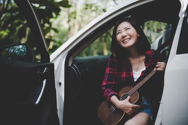 Mulher asiática da beleza que sorri e que tem o divertimento no verão do ar livre com o ukulele no carro branco.