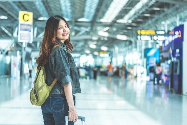 Mulher asiática da beleza que viaja e que guarda a mala de viagem no aeroporto.