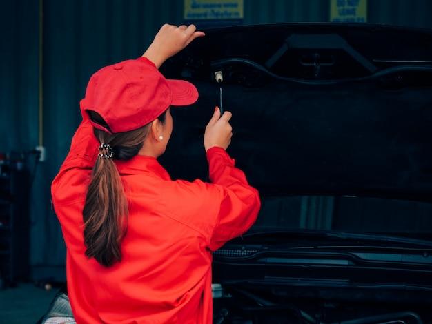 Mulher asiática da engenharia que fixa o carro.