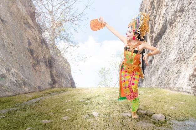 Mulher asiática dançando dança tradicional balinesa (dança kembang girang) ao ar livre