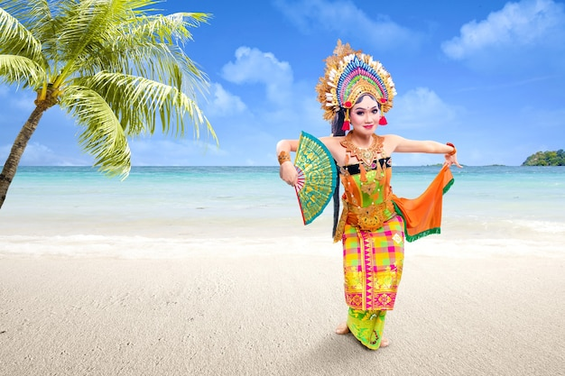 Mulher asiática dançando dança tradicional balinesa (dança kembang girang) na praia
