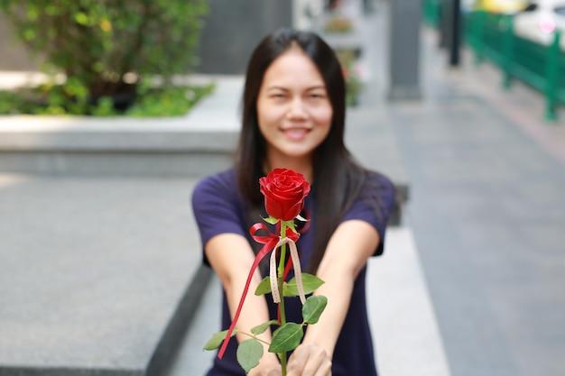 Mulher asiática dando a rosa para você. concentre-se na flor.