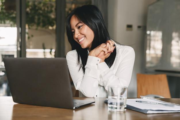 Mulher asiática de 20 anos, alegre, vestindo camisa branca, sorrindo e gesticulando com a mão de lado, enquanto olha para a tela do laptop no escritório