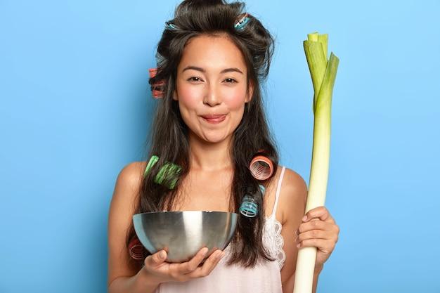 Mulher asiática de aparência agradável e satisfeita com cabelo escuro, segura uma tigela de aço e vegetais frescos, faz uma salada saborosa, tem longos cabelos escuros com rolos, usa roupa de dormir, posa dentro de casa