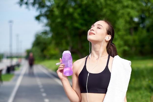 Mulher asiática de aptidão com garrafa de água e toalha após a execução de treinamento no parque de verão