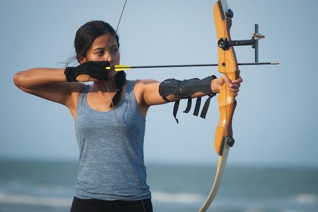 Mulher asiática de arco e flecha com arco tiro na praia
