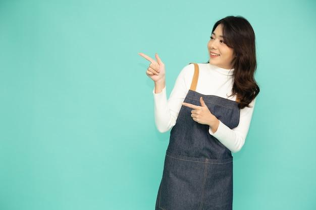 Mulher asiática de avental apontando o dedo para o lado em branco da cópia