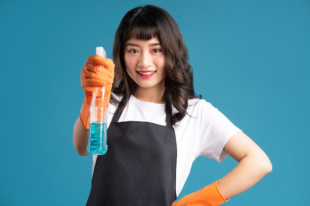 Mulher asiática de avental e luvas se preparando para o trabalho de limpeza