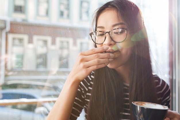 Mulher asiática de beleza comendo bolo no peitoril da janela