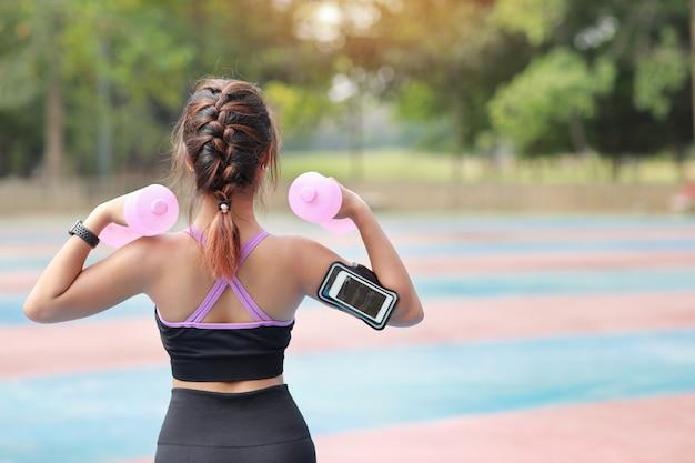 Mulher asiática de beleza traseira atlética vista traseira no sportswear em pé e levantando halteres ao ar livre para o exercício de manhã. a menina ativa dá certo no exercício do bíceps com fundo verde da árvore. conceito de esporte