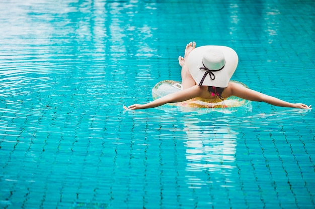 Mulher asiática de biquíni em viagem relaxando na piscina em resort com piscina