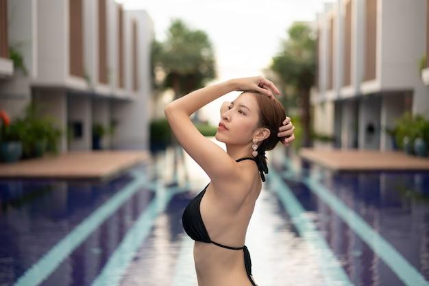 Mulher asiática de biquíni preto posando perto da piscina