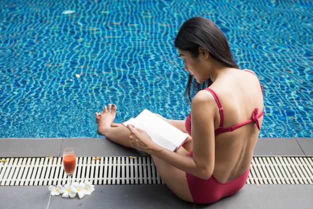 Mulher asiática de biquíni vermelho lendo um livro com um copo de suco à beira da piscina