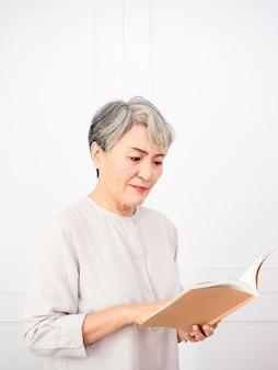 Mulher asiática de cabelo grisalho sênior segurando e lendo o livro em casa.
