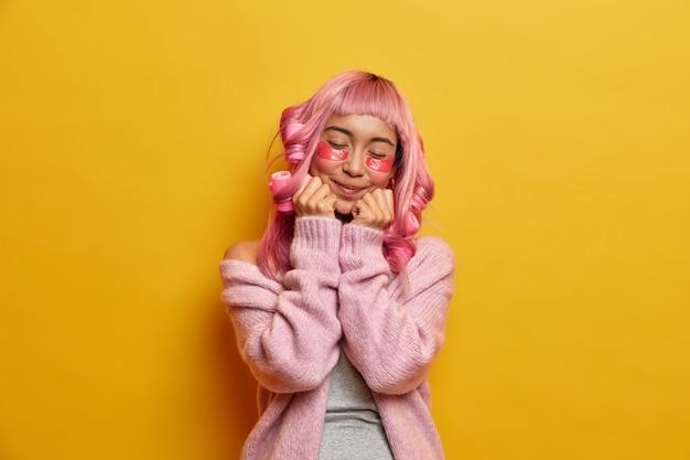Mulher asiática de cabelo rosa satisfeito satisfeita mantém as mãos embaixo do queixo, fecha os olhos, aplica rolos de cabelo