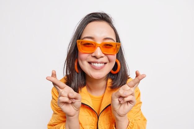 Mulher asiática de cabelos escuros na moda alegre faz desejo mantém os dedos cruzados espera pelo sonho se tornando realidade sorrisos feliz usa óculos de sol laranja da moda, brincos e jaqueta isolada sobre a parede branca