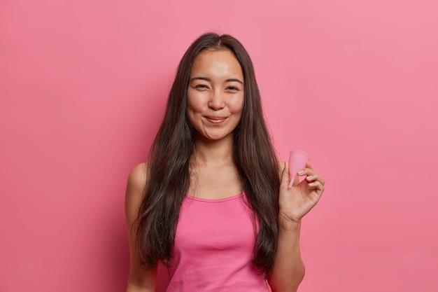Mulher asiática de cabelos escuros positiva segura o copo de menstruação feito de silicone ou borracha de látex como uma alternativa ecologicamente correta aos absorventes internos e externos, usados durante a menstruação para evitar vazamentos. ginecologia, menstruação