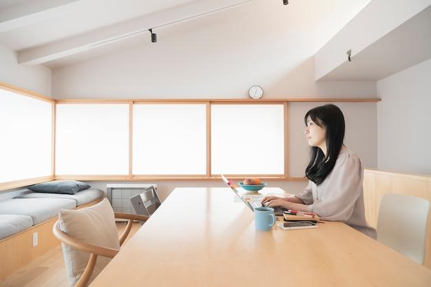 Mulher asiática de cabelos negros trabalhando em casa usando um laptop