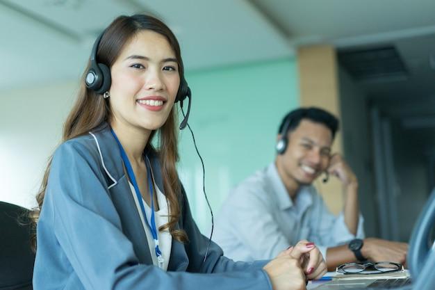Mulher asiática de call center com equipe trabalhando