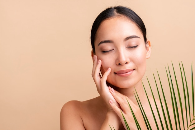 Mulher asiática de close-up com folhas