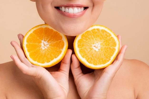 Mulher asiática de close-up com sorriso largo e laranja