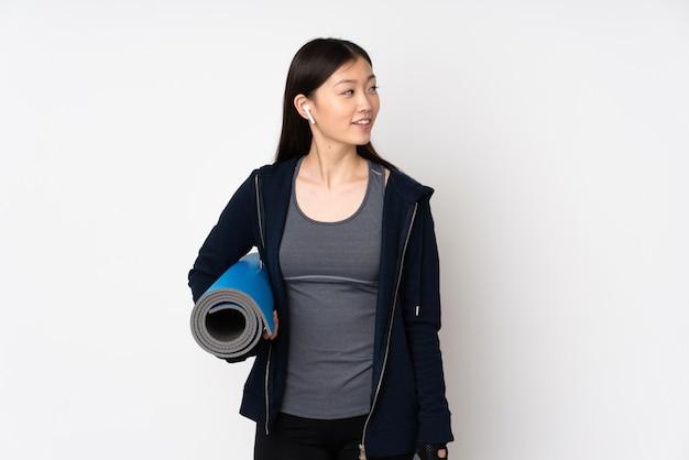 Mulher asiática de esporte jovem na parede branca com uma esteira e sorrindo