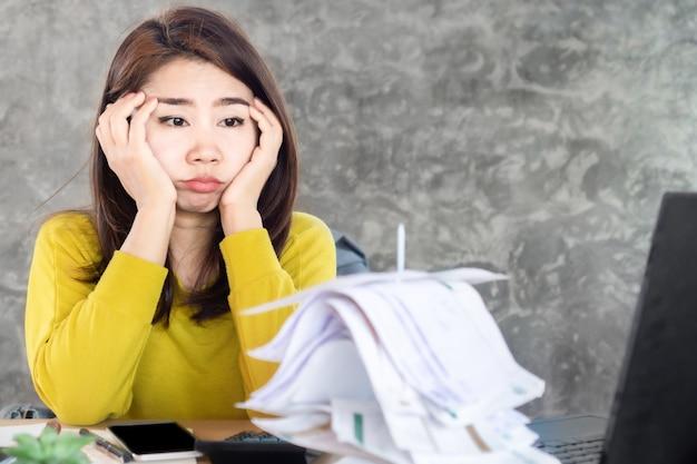 Mulher asiática de estresse olhando para contas financeiras não pagas