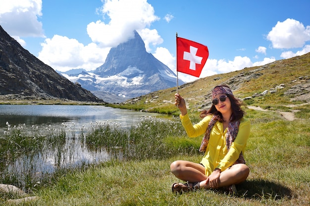 Mulher asiática de felicidade sentado e sorrindo segurando bandeira suíça perto do lago alpino de riffelhorn
