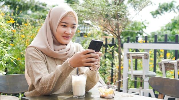 Mulher asiática de hijab jogando telefone em um café