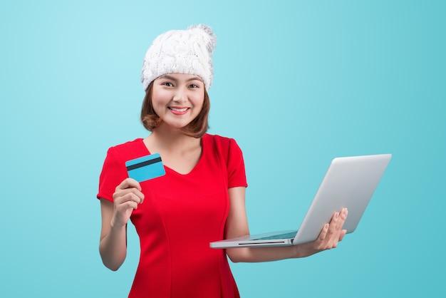 Mulher asiática de inverno segurando laptop e cartão de crédito contra vinheta azul
