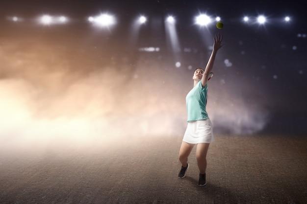 Mulher asiática de jogador de tênis com uma raquete de tênis e bola nas mãos dela, servindo a bola