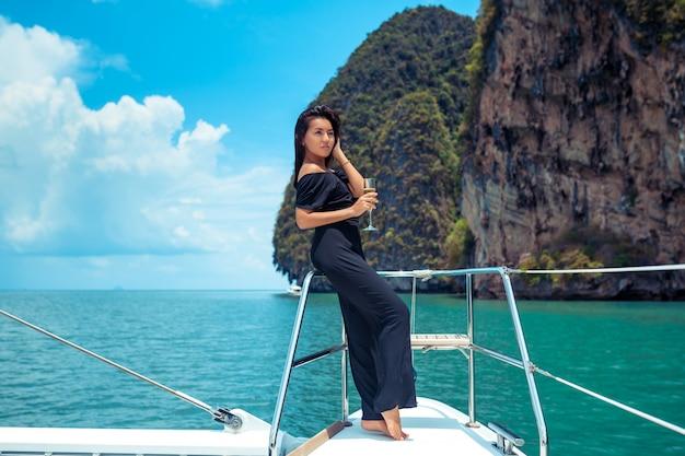Mulher asiática de luxo em vestido de noite preto, bebendo champanhe no convés de um iate
