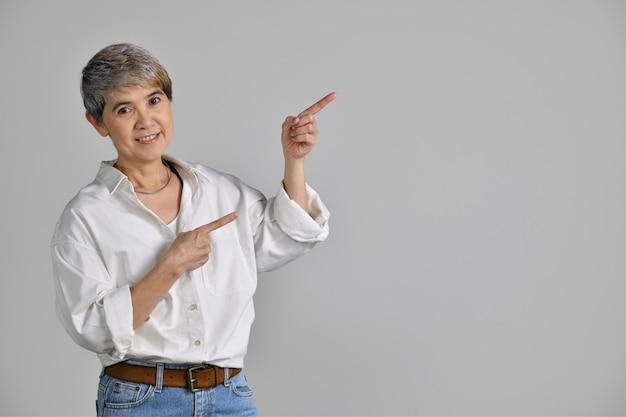 Mulher asiática de meia idade apontando os dedos para o espaço vazio da cópia para o texto isolado no fundo branco