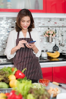 Mulher asiática de meia-idade bonita com um avental stading usando smartphone móvel conectar-se à internet na cozinha com um rosto sorridente e feliz. conceito de estilo de vida moderno de dona de casa.